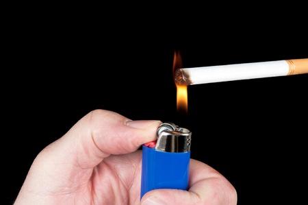 butane: A person lights a cigarette with a blue butane lighter.