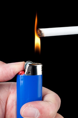 A person lights a cigarette with a blue butane lighter. photo