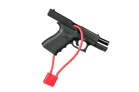 A hand gun firearm is locked with a safety cable to prevent anyone from firing the weapon. photo