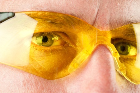 Close up of a man wearing yellow eye protective glasses