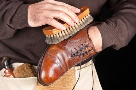 Een schoen shiner werkt op de definitieve afslijping van een jurk lederen schoen