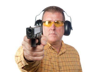 A man aims a handgun while wearing proper safety equipment such as safety glasses and hearing protection. Stock Photo - 8981628