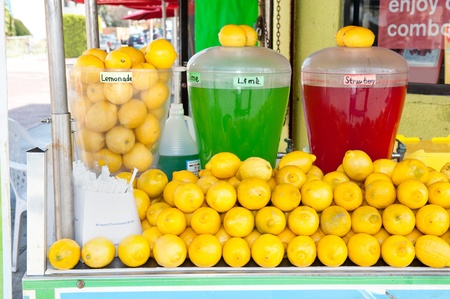 A lemonade stand with strawberry, lime and lemon flavored drinks.