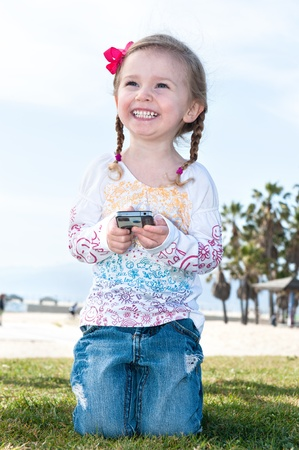 gripping hair: A beautiful little girl smiles after playing a video game. Stock Photo
