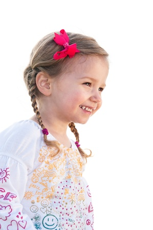 A smiling little thrtee year old girl with piggytails on a white background. photo