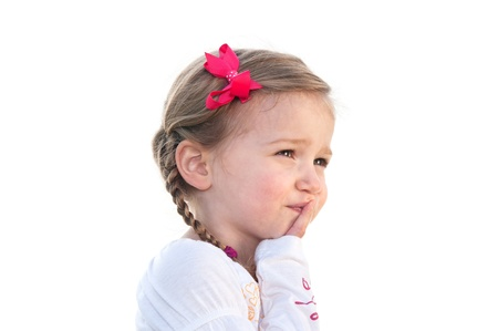 A little three year old girl on a white background thinking about something. photo