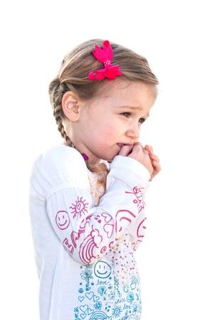 흰색 배경에 아름 다운 작은 소녀는 겁이며, 그녀의 얼굴에 그녀의 손을 보유하고있다. 스톡 콘텐츠