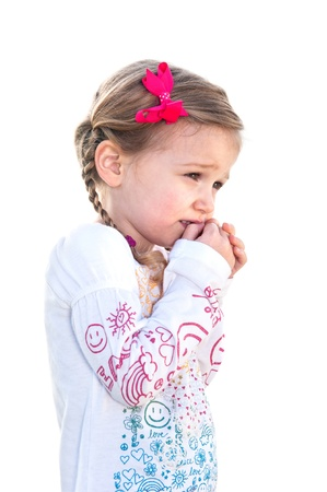 A beautiful little girl on a white background is frightened and holds her hand to her face.