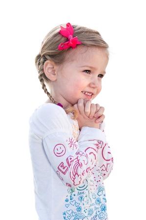 Een mooi klein meisje op een witte achtergrond is blij en houdt haar hand op haar gezicht.