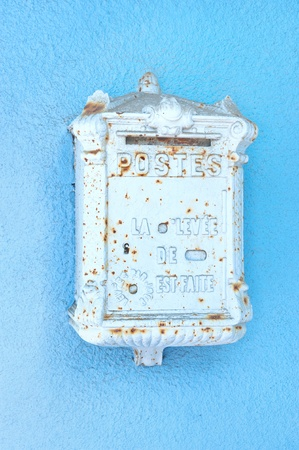 stucco wall: An antique mailbox from france mounted on a blue stucco wall Stock Photo