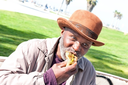 65 years old: An elderly homeless man eats a hotdog while relaxing in the park. Stock Photo