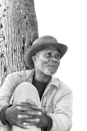 Een oude zwarte man met een sjofele grijze baard ontspant in een park op een zonnige dag. Stockfoto