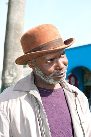 65 years old: An elderly black man with a scruffy gray beard relaxes at a park on a sunny day.