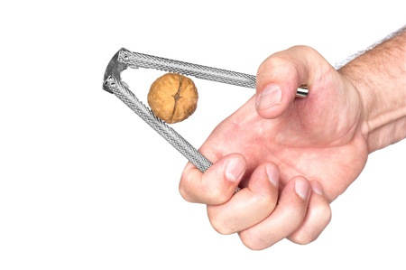 nut cracker: A man squeezes a walnut with a nut cracker. Stock Photo