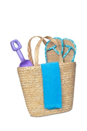 beachbag: A beachbag carrying a toy shovel, flip flops and a beach towel.