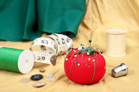 A sewing table with buttons, pin cushion, tape measure and thimble. Stock Photo