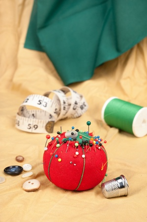 A sewing table with buttons, pin cushion, tape measure and thimble. photo