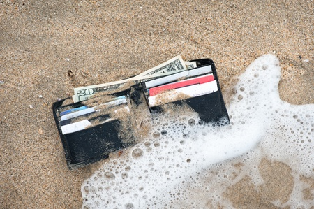 lost money: A lost wallet in the surf zone at the beach. Stock Photo