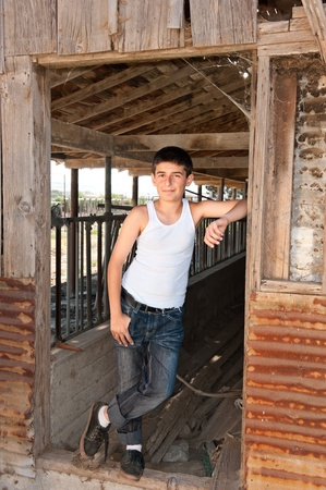 beater: A teenager in a rural area stands in the doorway of an old worn down barn Stock Photo
