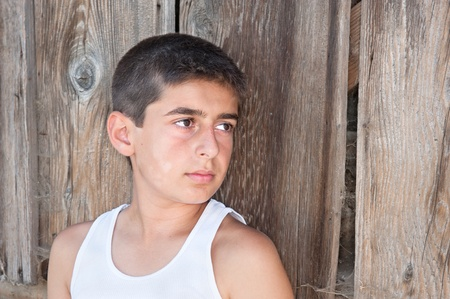 wife beater: A teenager in a rural area stands against an old worn down barn wall