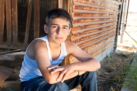 A young man sits in the doorway of an old abandoned barn in a rural area. Stock Photo