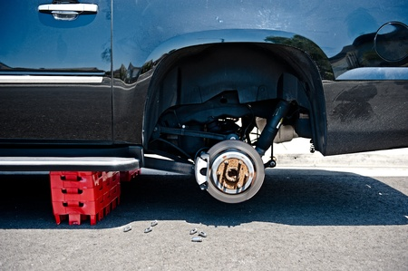 A car with stolen wheels is propped up with plastic containers.