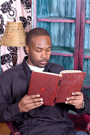 A black man reading a good book in his office.