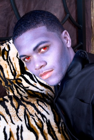 A black man with make-up to look like a vampire with red, evil eyes.