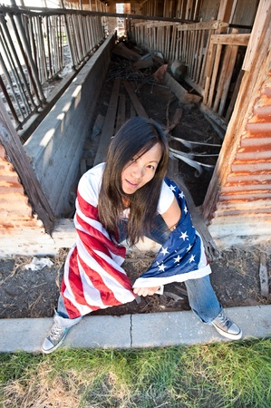 Patriotic Asian woman with an American flag sits on an old abandoned barn doorstep photo