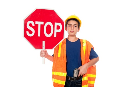 regulating: A boy directs traffic using a stop sign and a gun