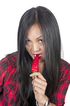 flannel: Beautiful Asian woman nibbling on a red hot pepper.
