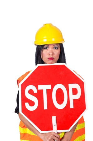 frowns: A sexy female construction worker frowns while holding a stop sign. Stock Photo