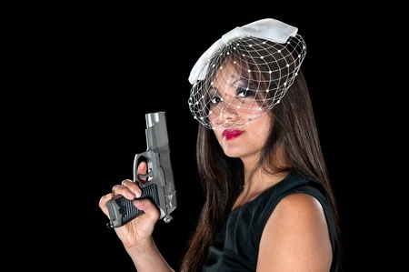 A beautiful, sinister Asian woman holding a pistol. Stock Photo - 10291446