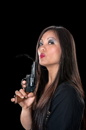 A beautiful, sinister Asian woman holding a pistol and blowing on the smoke coming out of the barrel.  Stock Photo - 10291451