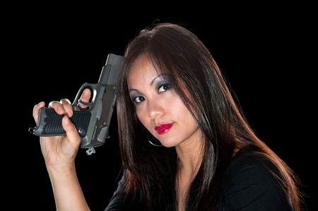 A beautiful, sinister Asian woman holding a pistol. Stock Photo - 10291448