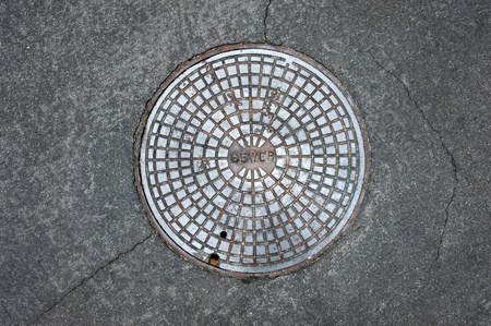 An old sewer manhole coversurrounded by an asphalt street Stock Photo