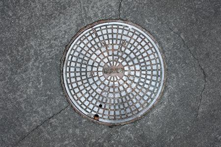 riool: Een oud riool mangat coversurrounded door een asfalt straat