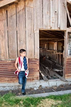 A patriotic teenager leaning against an old abandoned barn while holding an American flag. photo