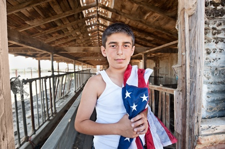 A patriotic teenager standing in the doorway of an old abandoned barn while holding an American flag. Reklamní fotografie