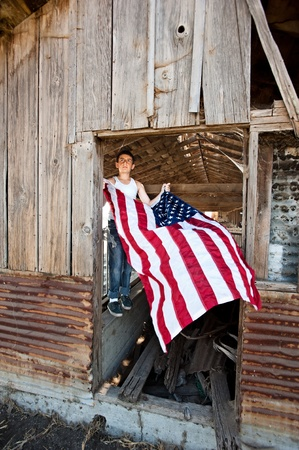 A patriotic teenager gets ready to hang an American flag on an old rustic barn photo