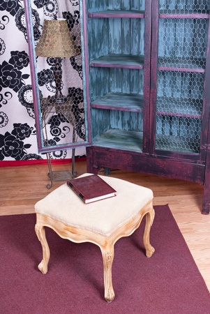 A book rests on a white ottoman in a home office