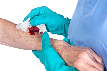 gloves nurse: A nurse tends to a bloody wound on an alderly woman Stock Photo