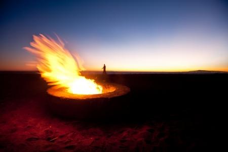 A couple walks along a beach behind a large fire during sunset.