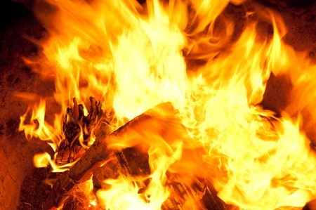 ignited: Close up of burning fire wood and flames. Image shows the charred wood and bright flames.