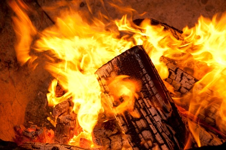 burnt wood: A close up of burning, charred wood with bright orange flames Stock Photo
