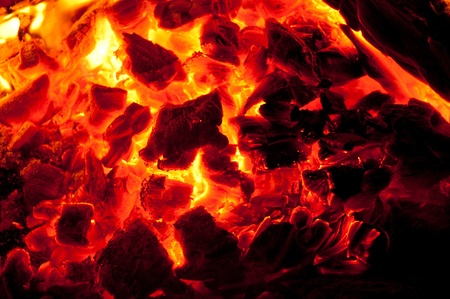 ignited: A blazing fire in a cement fire pit at the beach during night time. Stock Photo