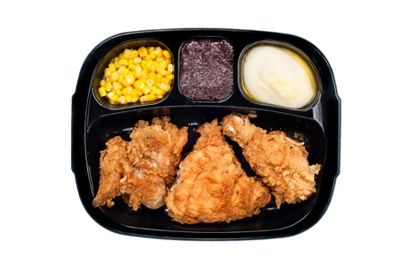 A cooked tv dinner of fried chicken, corn, mashed potatoes and dessert in a plastic black tray.