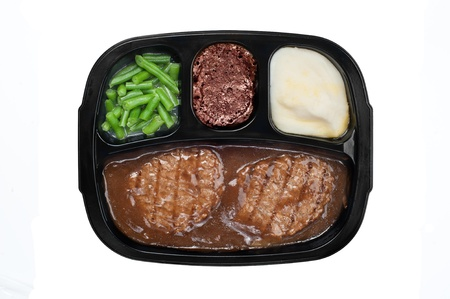 An unhealthy Salidbury steak TV dinner with gravy, mashed potatoes and a brownie dessert in a plastic tray isolated on white Banco de Imagens