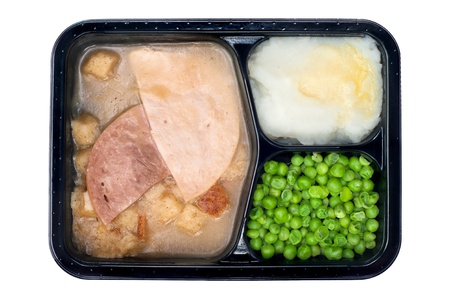A TV dinner consisting of turkey, ham, peas and mashed potatoes isolated on white photo