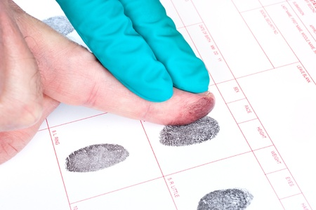 criminal law: A man is being finger printed for either a crime of for FBI screening on a legal document form.